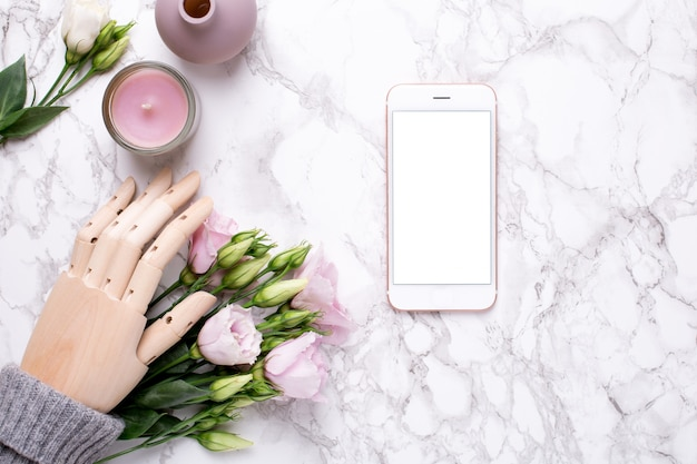 Mobiele telefoon en houten hand met roze bloemen op marmer
