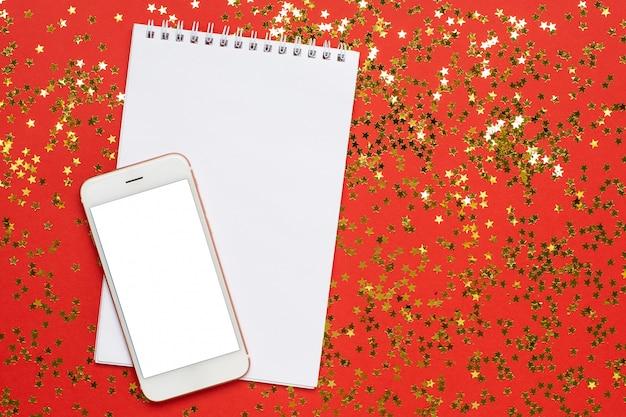 Mobiele telefoon en kladblok met gouden sterren confetti, kerstmis en nieuwjaar concept