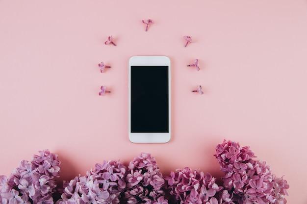 Mobiele telefoon en lila bloemen op roze pastel tafel