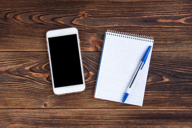 Mobiele telefoon en notitieboekje met pen
