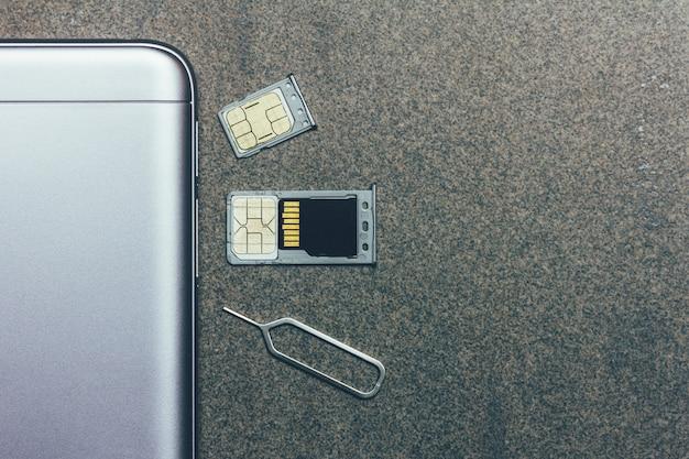 Mobiele telefoon en open slots voor nano-simkaarten, micro sd-schijf en metalen sleutel op grijs met copyspace