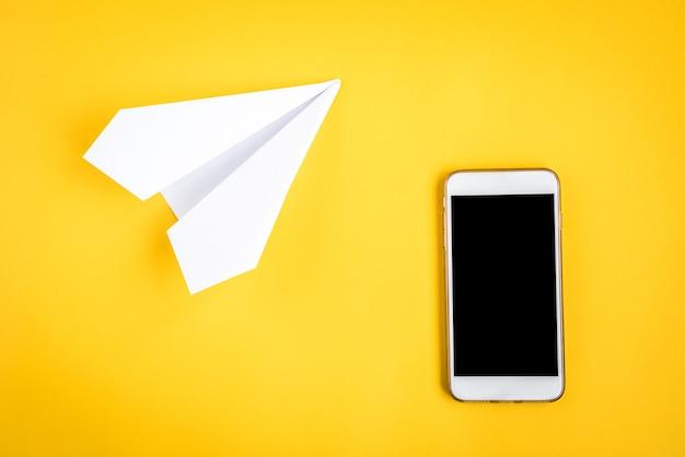 Mobiele telefoon en papieren vliegtuigje op geel