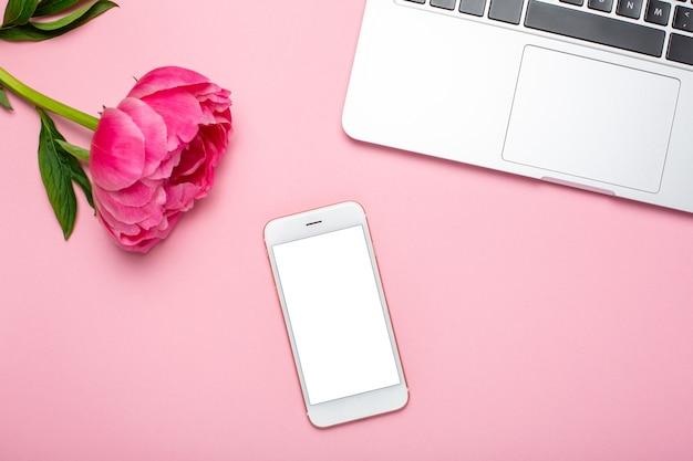 Mobiele telefoon en pioenroos bloem op roze pastel tafel in plat lag stijl. vrouwelijk bureau.