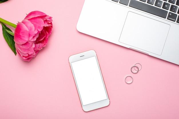 Mobiele telefoon en pioenroos bloem op roze pastel tafel in plat lag stijl.