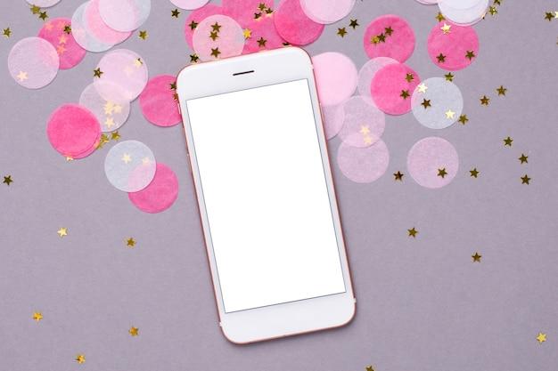 Mobiele telefoon en roze confetti met gouden sterren op grijs