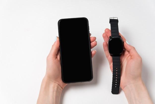 Mobiele telefoon en smart frequent in vrouwelijke handen op witte achtergrond. gadgets van de moderne mens. kopieer ruimte