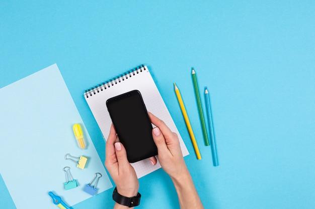 Mobiele telefoon en verschillende briefpapier geïsoleerd op whitte en blauwe achtergrond