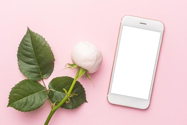 Mobiele telefoon en witte rozen op pastel roze achtergrond met copyspace. vakantie- en liefdesartikel