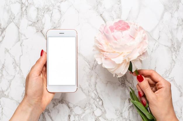 Mobiele telefoon in de hand met een witte en roze piony bloemen op een marmeren oppervlak