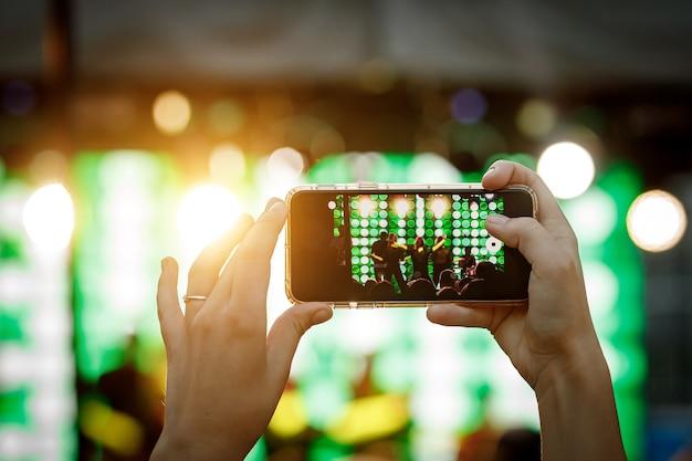 Mobiele telefoon in de hand tijdens het filmen van een concert