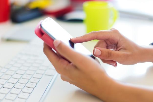 Mobiele telefoon in de hand van een vrouw. binnenbeeld.