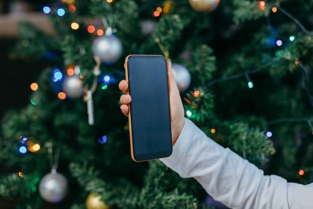 Mobiele telefoon in de handen van een meisje tegen de achtergrond van een nieuwe jaarboom. online groeten voor het nieuwe jaar. online winkelen.
