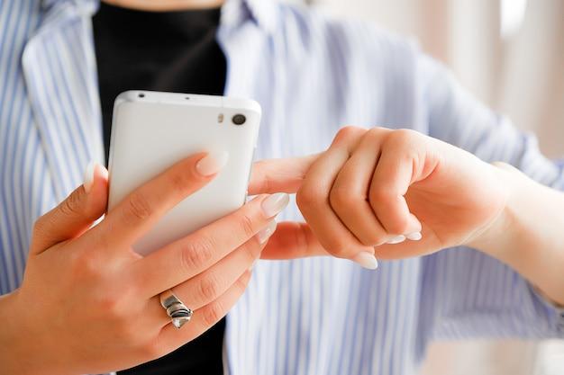 Mobiele telefoon in de handen van een stijlvolle mode meisje freelancer. een jonge vrouw in een zwart t-shirt en een gestreept shirt, met een prachtige manicure die de telefoon vasthoudt.