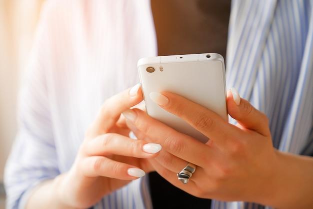 Mobiele telefoon in de handen van een stijlvolle vrouw of freelancer.