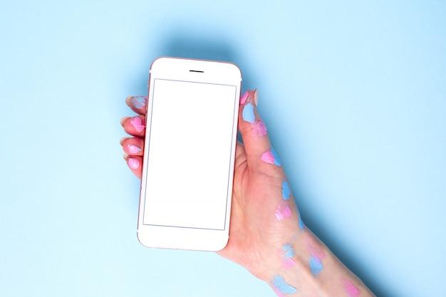 Mobiele telefoon in vrouwenhanden met waterverf op blauwe oppervlakte