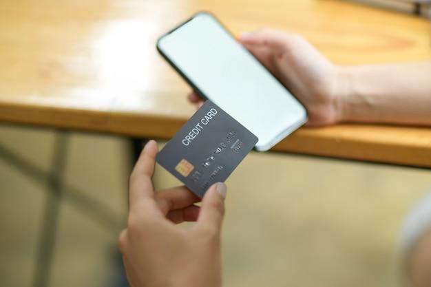 Mobiele telefoon leeg scherm mock-up met hold-creditcard, online betalingsconcept