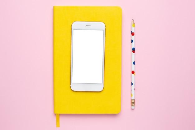Mobiele telefoon met een geel notitieboekje en een kleurrijk potlood op een roze bovenaanzicht als achtergrond