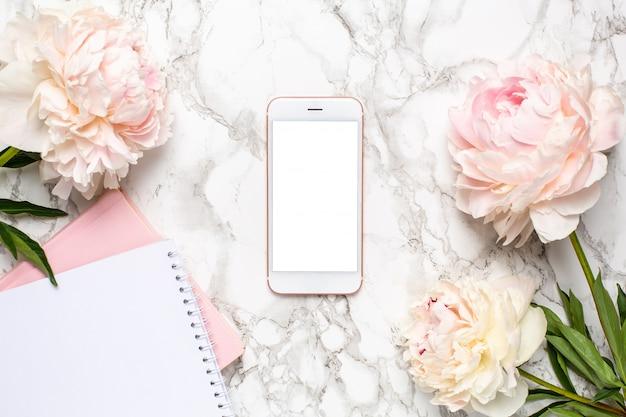 Mobiele telefoon met een wit en roze notitieboekje en piony bloemen op een marmeren achtergrond