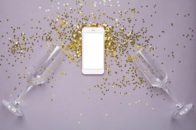 Mobiele telefoon met gouden sterren confetti op paars