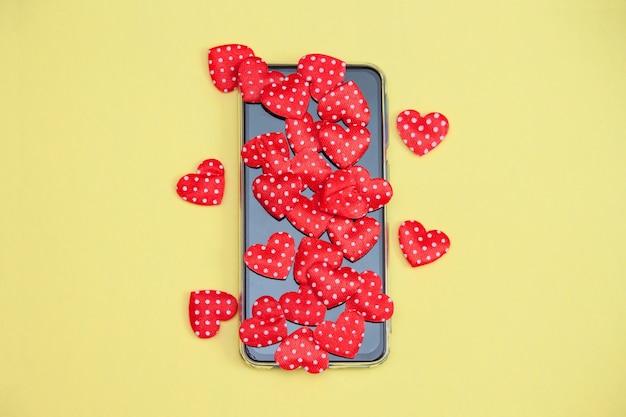 Mobiele telefoon met hartjes, liefde, valentijnskaartdagconcept.