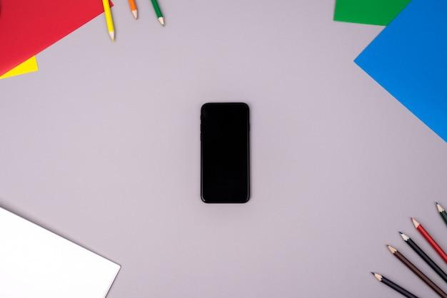 Mobiele telefoon met kleurenpotloden en gekleurd document op grijs