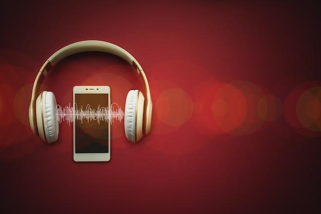 Mobiele telefoon met leeg scherm en koptelefoon op rode achtergrond met audiotrack.