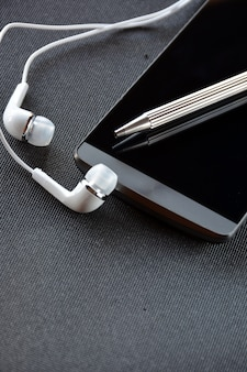 Mobiele telefoon met pen en koptelefoon