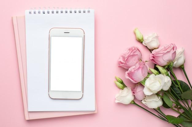 Mobiele telefoon met roze en witte rozen bloemen. minimalistische samenstelling voor de feestdagen, valentijnsdag en womens dag.