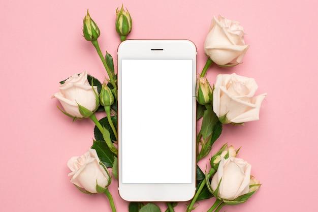 Mobiele telefoon met rozenbloemen op roze pastelkleurachtergrond, het concept van de vrouwentechnologie