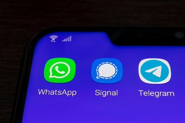 Mobiele telefoon met signal-, telegran- en whatsapp-applicaties, allemaal voor het verzenden van berichten