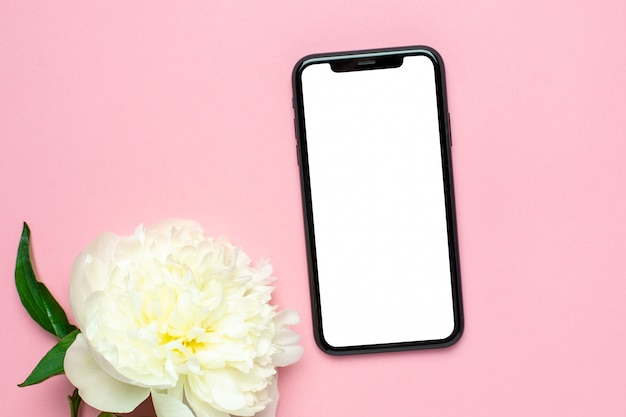 Mobiele telefoon mock up en pioen bloem op roze pastel tafel. vrouw werkbureau. zomer kleur