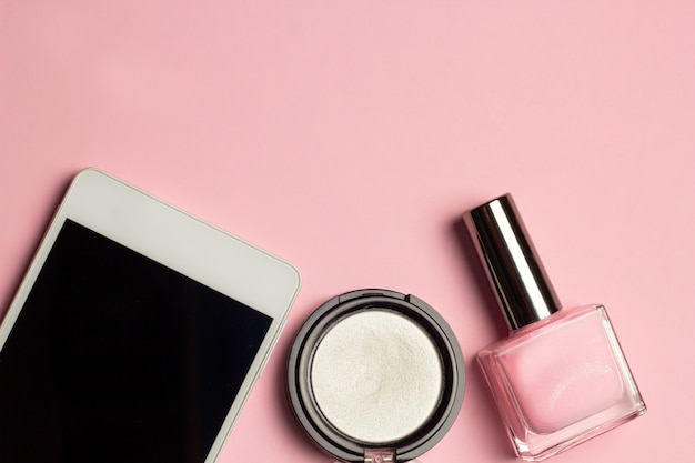 Mobiele telefoon, nagellak, oogschaduw mode plat leggen top weergave frame roze pastel achtergrond
