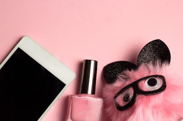 Mobiele telefoon, nagellak, schattige pluizige speelgoed mode plat leggen bovenaanzicht frame roze pastel achtergrond