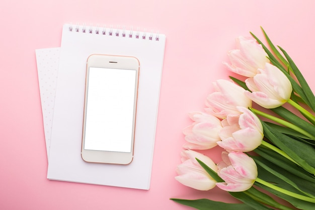 Mobiele telefoon, notebook en lentebloem roze tulpen. plat lag