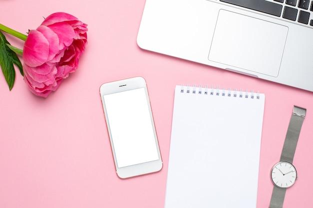 Mobiele telefoon, notebook en pioenroos bloem op roze pastel tafel in plat lag stijl. vrouwelijk bureau.