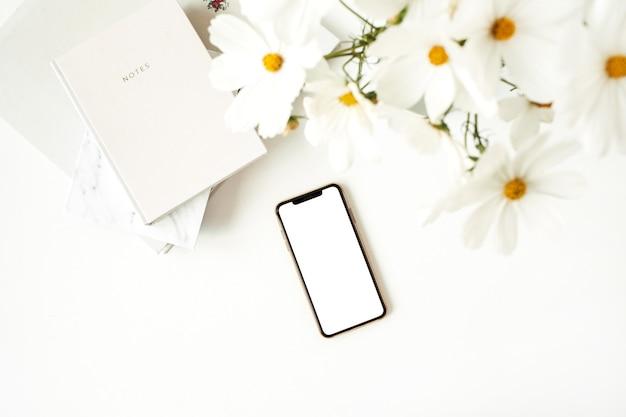Mobiele telefoon op witte tafel met madeliefjes en notebooks.
