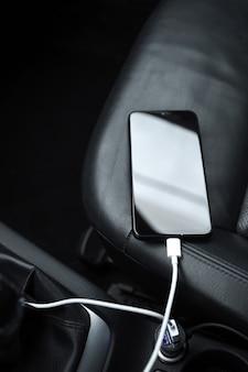 Mobiele telefoon, smartphone laadbatterij, opladen in de autostekker van dichtbij
