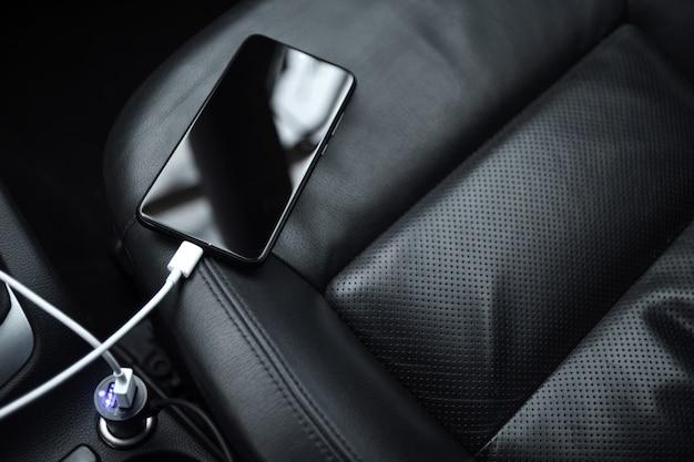 Mobiele telefoon, smartphone laadt batterij op, laadt op in de autostekker van dichtbij