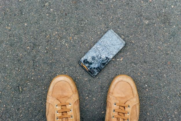 Mobiele telefoon viel op de grond terwijl de eigenaar naar de telefoon staarde met een gebroken scherm