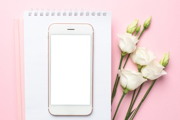 Mobiele telefoon, witte bloem en notitieblok op roze