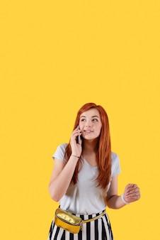 Mobiele verbinding. aangename aantrekkelijke vrouw die telefoneert terwijl hij tegen een gele achtergrond staat