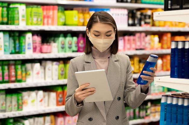 Mobiele vrouwelijke koper die smartphone gebruikt over winkelwagentje met papieren zakken met voedselproducten tijdens een bezoek aan de supermarkt