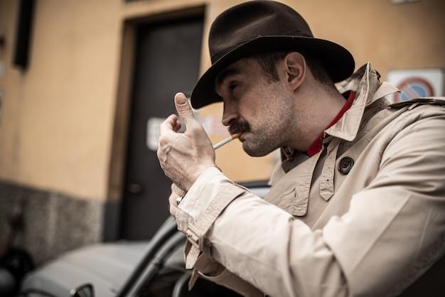 Mobster die een sigaret opsteekt tijdens het wachten voor een vintage auto