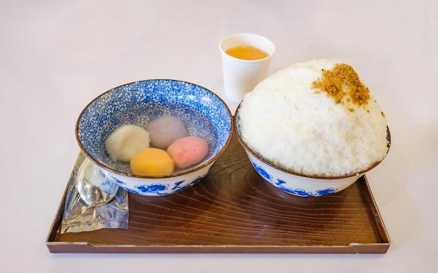 Mochi bingsu-kom met melkgeschoren ijs gegarneerd met gemberpoeder geserveerd met een kom met plakkerige rijstbal