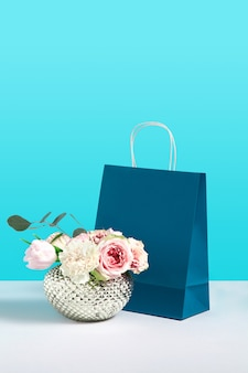 Mock up afbeelding met roze bloemen in vaas in de buurt van papier cadeauzakje staan op blauwe achtergrond. het conceptbeeld van de gift met ruimte voor ontwerp. bloemenwinkel. branding mock up. concept voor verkoop of kortingen