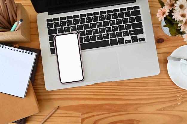 Mock-up beeld van slimme telefoon met leeg scherm, laptop en briefpapier op houten tafel.