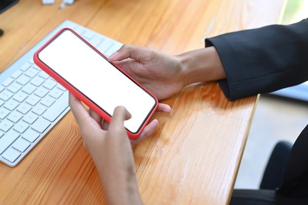 Mock-up beeld van zakenvrouw met slimme telefoon met wit scherm op houten bureau.