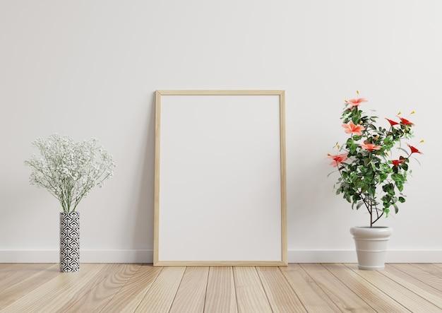 Mock-up fotolijst in de kamer, witte muur op de houten vloer, versierd met planten aan elke kant. 3d-weergave.