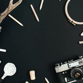 Mock-up frame gemaakt van retro camera, handgemaakte lepel, potloden en accessoires op zwart krijtbord