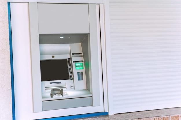 Mock up, geldautomaat in de stad. tegen de achtergrond van witte rolgordijnen.